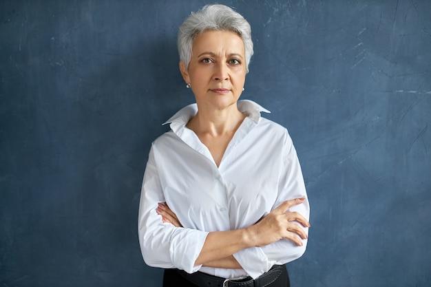Pewna europejska 50-letnia kobieta agentka nieruchomości w eleganckiej odzieży pozuje na białym tle z rękami założonymi na piersi