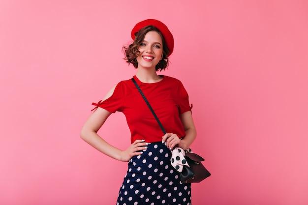 Pewna francuska dama pozuje ze szczerym uśmiechem. romantyczna kaukaski kobieta w czerwonym berecie wyrażająca pozytywne emocje.