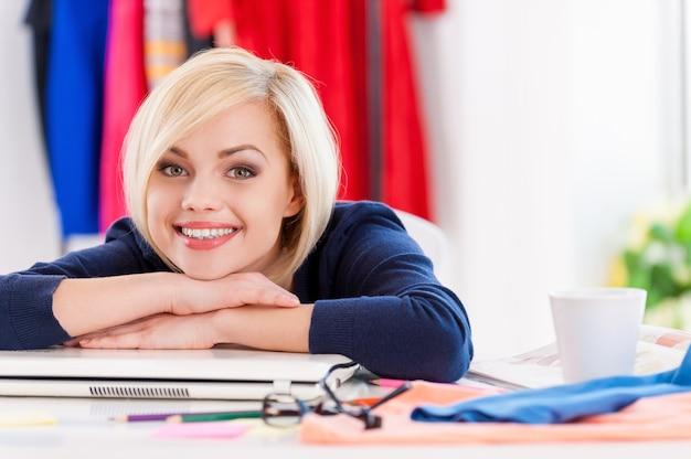 Pewna i kreatywna bizneswoman. piękna młoda kobieta trzymająca się za ręce na brodzie i uśmiechnięta siedząc w swoim miejscu pracy
