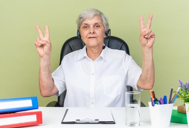 Pewna kaukaska kobieta call center operator na słuchawkach siedzących przy biurku z narzędziami biurowymi gestem znaku zwycięstwa na zielonej ścianie