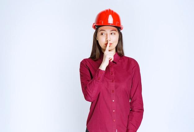 Pewna kobieta architekt w czerwonym kasku twardym pokazując znak ciszy.