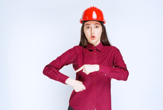 Pewna kobieta architekt w czerwonym kasku twardym stojąc i wskazując.