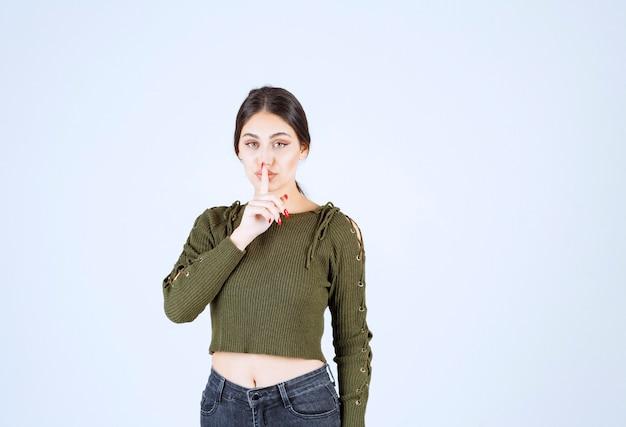 Pewna kobieta stojąc i dając znak ciszy na białym tle.