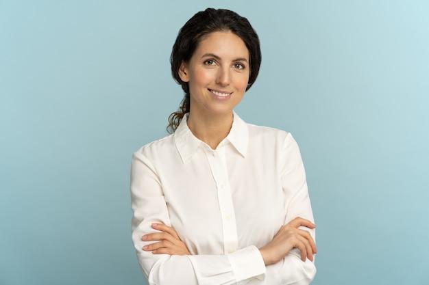 Pewna kobieta, uśmiechnięta, patrząc na kamery, skrzyżowanymi rękami, pozowanie na białym tle na niebieskim tle