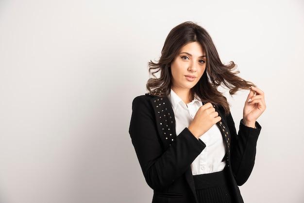 Pewna kobieta w czarnej kurtce pozuje na białym