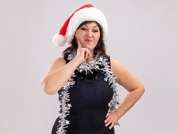 Pewna kobieta w średnim wieku nosząca santa hat i blichtrową girlandę wokół szyi patrząc na aparat trzymając rękę na talii i podbródku na białym tle