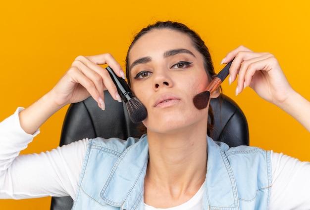 Pewna ładna kaukaska kobieta siedzi przy stole z narzędziami do makijażu, stosując rumieniec za pomocą pędzli do makijażu na białym tle na pomarańczowej ścianie z miejsca na kopię