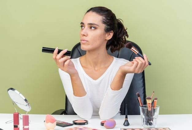 Pewna ładna kaukaska kobieta siedzi przy stole z narzędziami do makijażu, trzymając pędzel do makijażu i patrząc na bok izolowane na oliwkowozielonej ścianie z miejsca na kopię