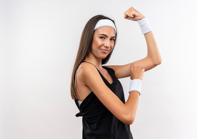 Pewna ładna sportowa dziewczyna nosząca opaskę i nadgarstek, gestykulując mocno i dotykając jej ramienia na białym tle na białej ścianie z miejscem na kopię