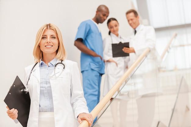 Pewna lekarka. pewna siebie lekarka schodzi na dół i uśmiecha się, podczas gdy jej koleżanki rozmawiają w tle