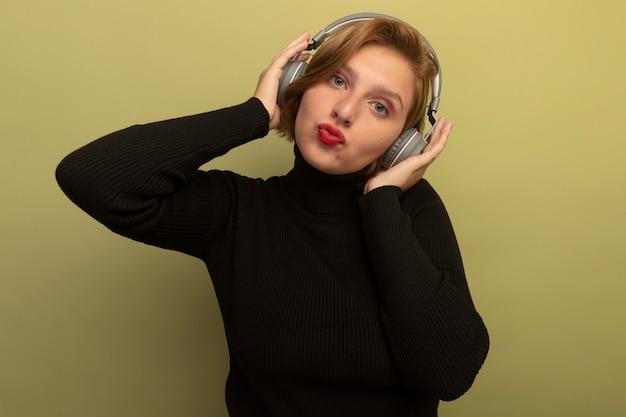 Pewna młoda blondynka w słuchawkach, kładąc na nich ręce, wykonując gest pocałunku