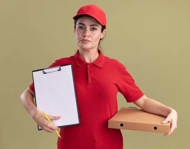 Pewna młoda dostawcza kobieta w mundurze i czapce trzymająca paczkę pizzy pokazująca schowek z ołówkiem w dłoni odizolowana na oliwkowozielonej ścianie