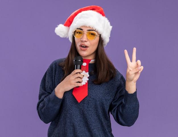 Pewna młoda kaukaska dziewczyna w okularach przeciwsłonecznych z santa hat i santa krawat gestykuluje znak zwycięstwa i trzyma mikrofon udając śpiewać na fioletowej ścianie z kopią miejsca