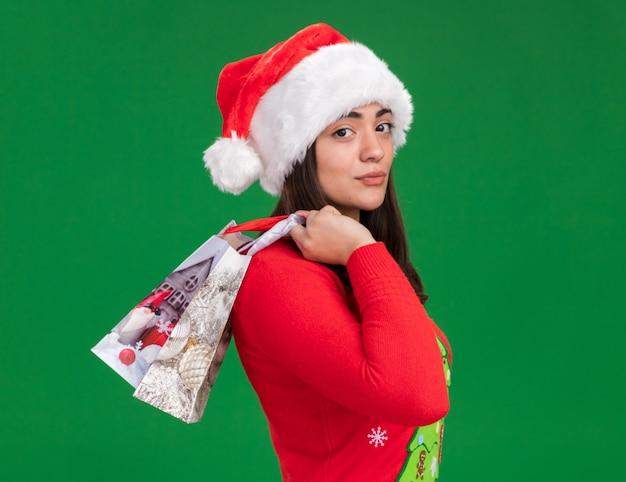 Pewna młoda kaukaska dziewczyna z santa hat stoi bokiem trzymając papierową torbę na prezent odizolowaną na zielonej ścianie z kopią przestrzeni