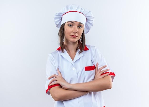 Pewna młoda kobieta kucharz w mundurze szefa kuchni, skrzyżowanie rąk na białym tle