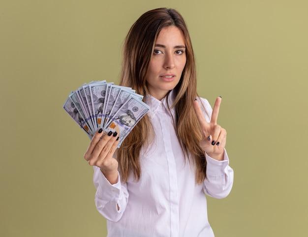 Pewna młoda ładna kaukaska dziewczyna trzyma pieniądze i gesty zwycięstwa ręka znak