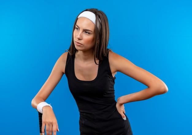 Pewna młoda ładna sportowa dziewczyna nosi opaskę i nadgarstek, kładąc ręce na kiju bejsbolowym i na talii, patrząc na bok na białym tle na niebieskiej ścianie