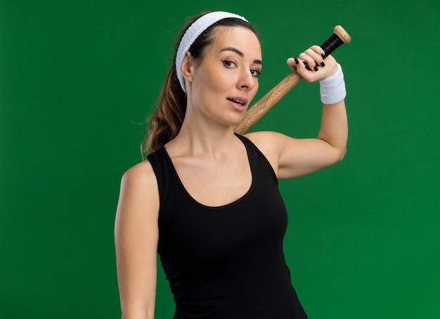 Pewna młoda ładna sportowa dziewczyna nosząca opaskę i opaski na rękę trzymająca kij bejsbolowy odizolowana na zielonej ścianie z miejscem na kopię