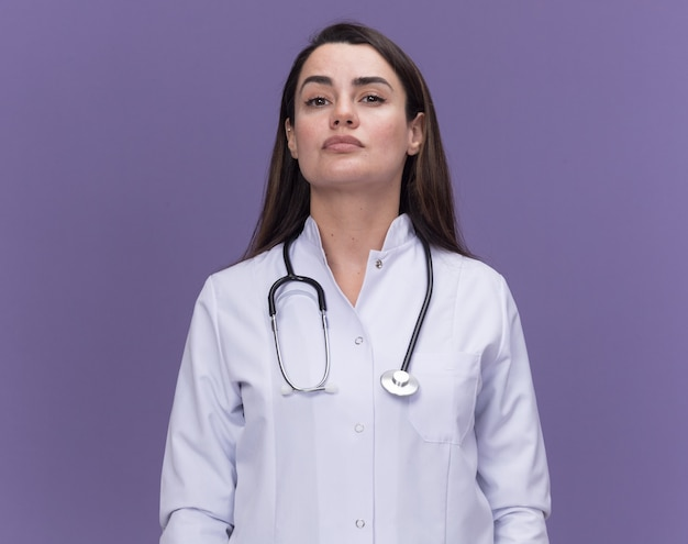 Pewna młoda lekarka nosząca szatę medyczną ze stetoskopem odizolowaną na fioletowej ścianie z miejscem na kopię