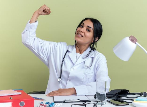 Pewna młoda lekarka nosząca szatę medyczną ze stetoskopem siedzi przy biurku z narzędziami medycznymi, wykonując silny gest odizolowany na oliwkowozielonej ścianie
