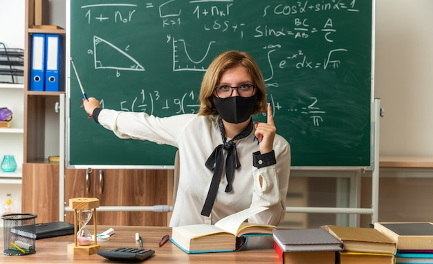 Pewna młoda nauczycielka w okularach i masce medycznej siedzi przy stole z narzędziami szkolnymi wskazuje na tablicę z kijem wskaźnikowym w klasie