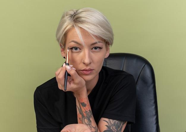 Pewna młoda piękna dziewczyna nakłada cień do powiek za pomocą pędzli do makijażu odizolowana na oliwkowozielonej ścianie