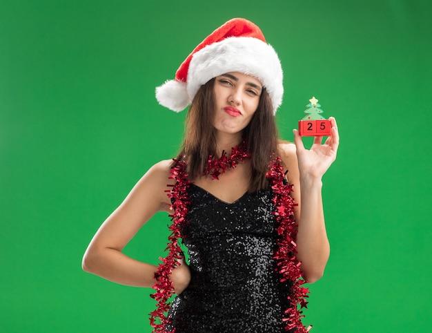 Pewna młoda piękna dziewczyna ubrana w świąteczny kapelusz z girlandą na szyi, trzymając świąteczną zabawkę kładąc rękę na biodrze na białym tle na zielonej ścianie
