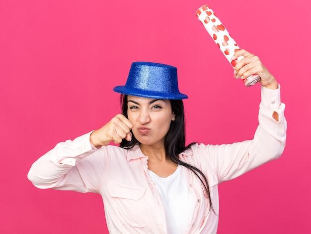Pewna młoda piękna dziewczyna w kapeluszu imprezowym trzymająca armatę konfetti na różowej ścianie