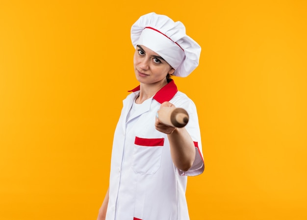 Pewna młoda piękna dziewczyna w mundurze szefa kuchni trzymająca wałek do ciasta w aparacie