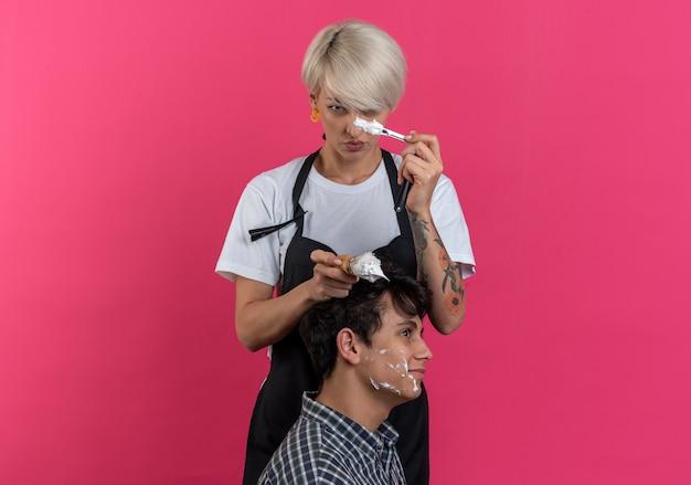 Pewna młoda piękna kobieta fryzjer w mundurze trzymająca narzędzia fryzjerskie i goląca brodę dla faceta izolowanego na różowej ścianie