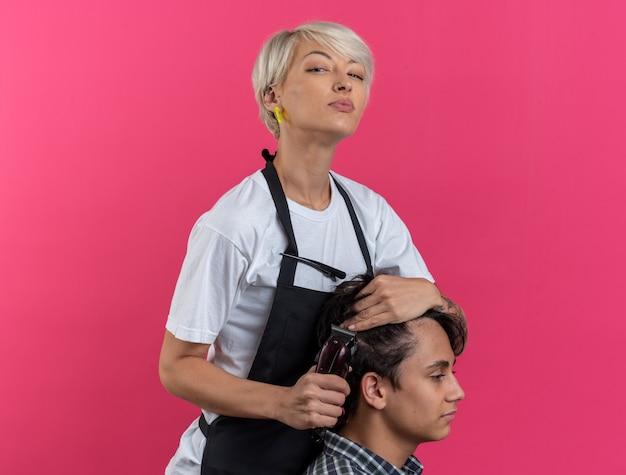 Pewna młoda piękna kobieta fryzjer w mundurze trzymająca narzędzia fryzjerskie i robiąca fryzurę dla chłopca izolowanego na różowej ścianie