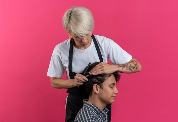 Pewna młoda piękna kobieta fryzjerka w mundurze robi fryzurę dla chłopca izolowanego na różowej ścianie