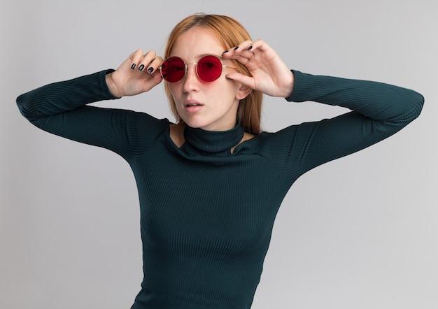 Pewna młoda rudowłosa imbirowa dziewczyna z piegami w okularach przeciwsłonecznych trzymająca się za ręce blisko twarzy na białym tle na białej ścianie z kopią przestrzeni
