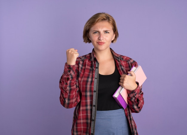 Pewna młoda słowiańska studentka trzyma pięść trzyma książkę i notatnik