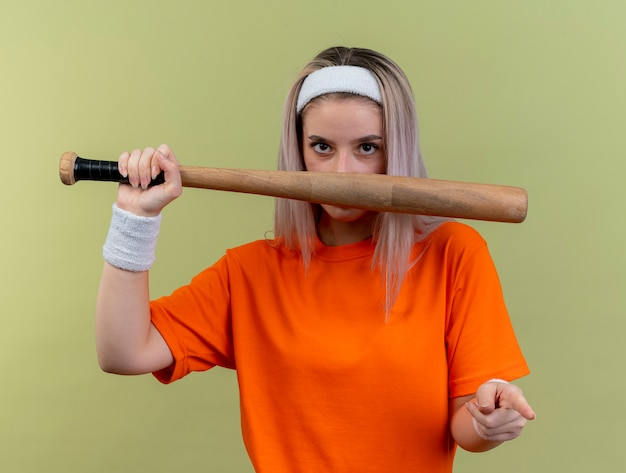 Pewna młoda sportowa dziewczyna rasy kaukaskiej z szelkami na sobie opaskę na głowę i opaski, trzymająca kij bejsbolowy i wskazująca na kamerę