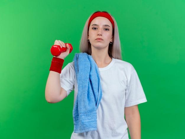 Pewna młoda sportowa dziewczyna rasy kaukaskiej z szelkami, nosząca opaskę na głowę i opaski z ręcznikiem na ramieniu, trzyma hantle