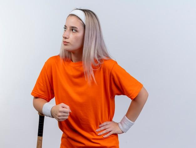 Pewna młoda sportowa dziewczyna rasy kaukaskiej z szelkami w opasce i opaskach na nadgarstku kładzie rękę na kiju bejsbolowym i patrzy z boku
