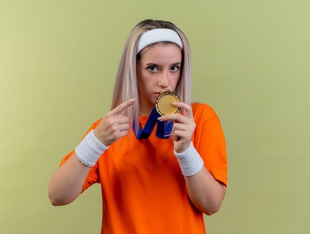 Pewna młoda sportowa dziewczyna rasy kaukaskiej z szelkami w opasce i opaskach trzyma i wskazuje złoty medal