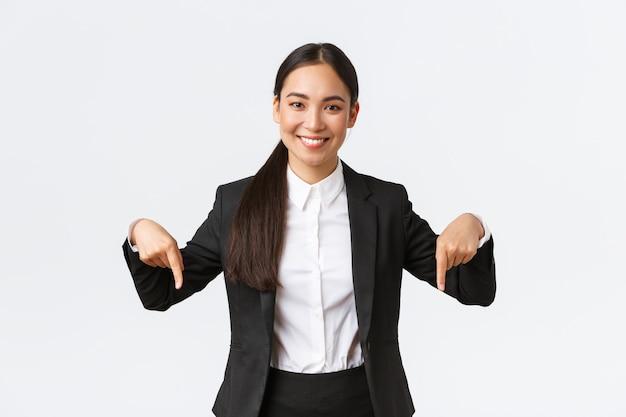 Pewna profesjonalna sprzedawczyni proponuje dobrą ofertę, najlepsze ceny. uśmiechnięta atrakcyjna kobieta agenta nieruchomości pokazująca dolną reklamę. kobieta w garniturze wskazując palcami w dół