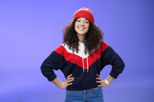 Pewna reklama podekscytowana urocza europejska kobieta z kręconą fryzurą w ciepłej czapce i stylowej bluzie trzymająca się za ręce w talii i uśmiechnięta przyjaźnie do kamery, gotowa do wyjścia i zabawy na zewnątrz.