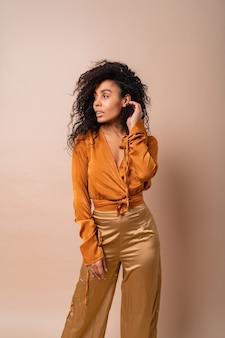 Pewna siebie afrykańska kobieta z idealnymi kręconymi włosami w swobodnej pomarańczowej bluzce i złotych spodniach pozuje na beżowej ścianie.