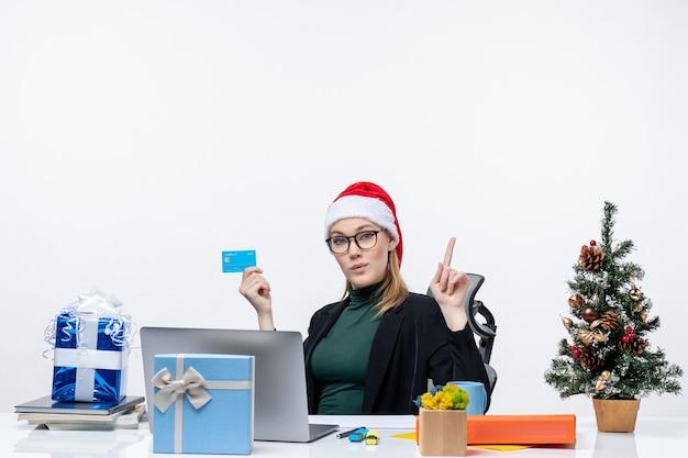Pewna siebie ambitna atrakcyjna kobieta w kapeluszu świętego mikołaja i okularach siedzi przy stole i trzyma kartę bankową i wskazuje powyżej w biurze