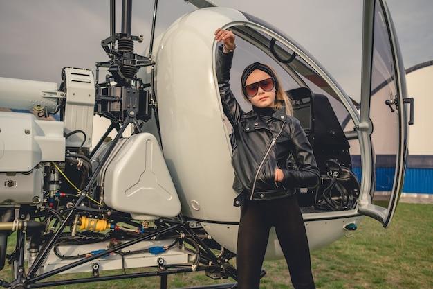 Pewna siebie animowana dziewczyna opierając się na otwartym kokpicie helikoptera