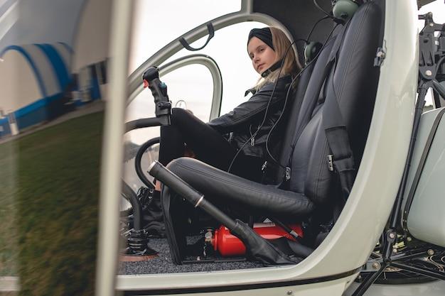 Pewna siebie animowana dziewczyna siedzi na siedzeniu drugiego pilota w helikopterze