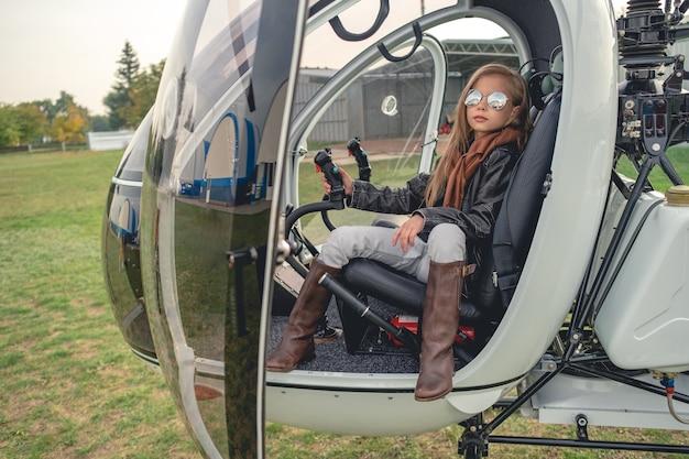 Pewna siebie animowana dziewczyna w lustrzanych okularach siedząca w helikopterze