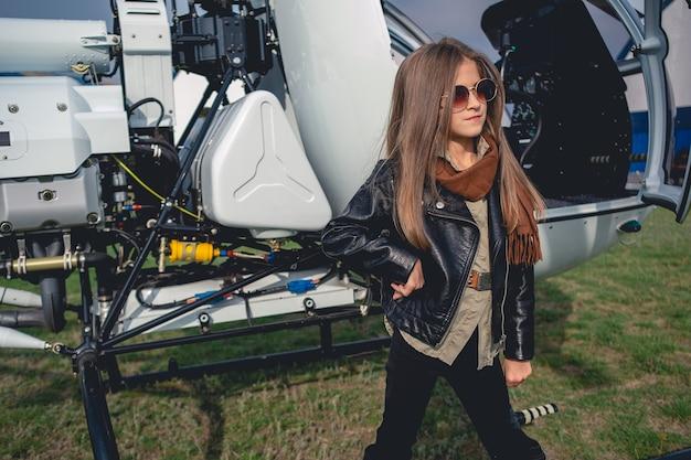Pewna siebie animowana dziewczyna w okularach przeciwsłonecznych stojąca w pobliżu otwartego helikoptera