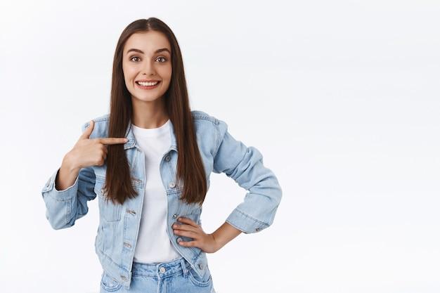 Pewna siebie, asertywna młoda brunetka wskazująca siebie, stojąca prosto z ręką na biodrze, mówiąca o osobistych osiągnięciach, przechwalania się lub chełpienia się, wolontariuszka, chce zostać kandydatem
