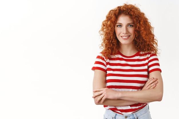 Pewna siebie atrakcyjna młoda rudowłosa, entuzjastyczna dziewczyna rozpoczynająca nowy projekt, zdeterminowana, zmotywowana do sukcesu, skrzyżowane ramiona