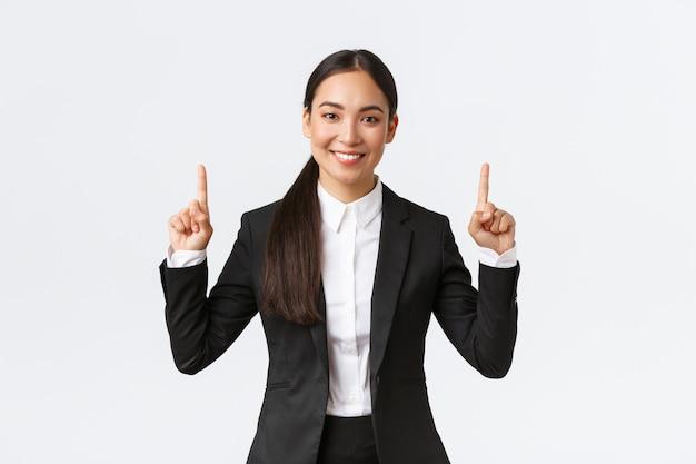 Pewna siebie azjatycka bizneswoman ma świetną propozycję dla klienta, wskazując palcem w górę na ogłoszenie lub ofertę specjalną. agent nieruchomości sprzedający dom, pokazujący baner, białe tło