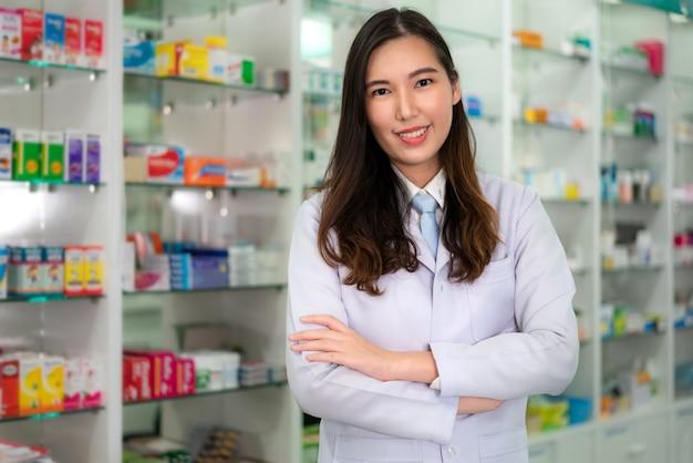 Pewna siebie azjatycka młoda farmaceutka z pięknym przyjaznym uśmiechem stojącym z założonymi rękami w aptece. pojęcie medycyny, farmacji, opieki zdrowotnej i ludzi.